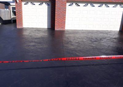 dark driveway freshly painted in front of white garage