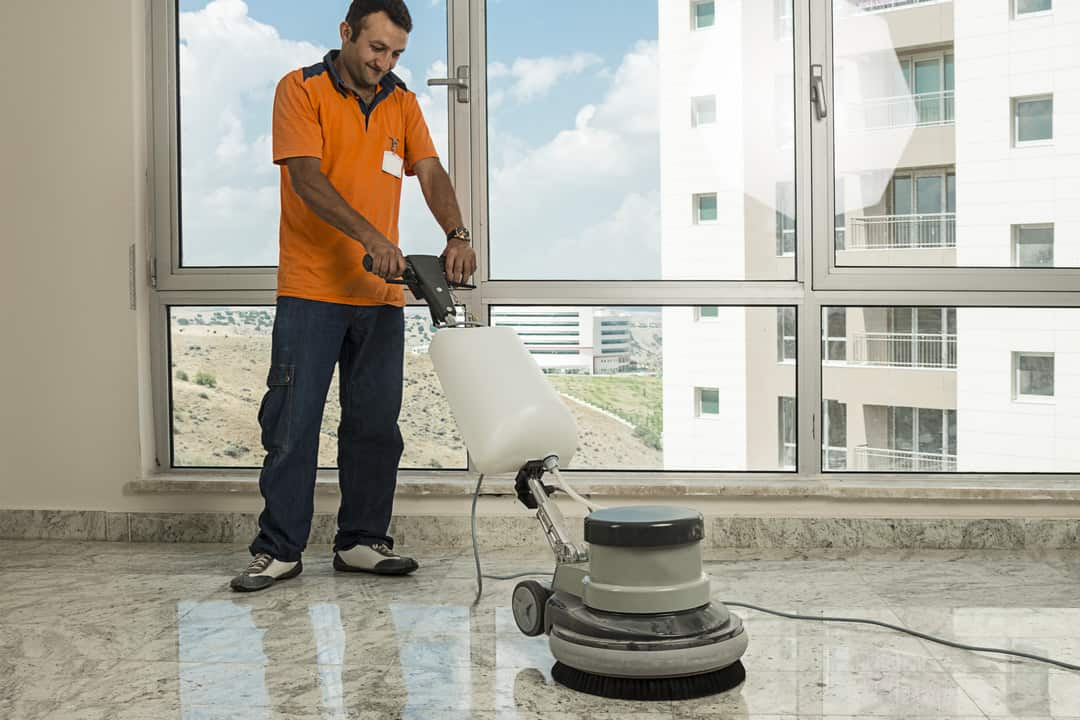 Worker wearing uniform cleaning marble floor with buffer