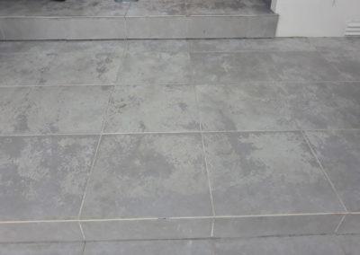 dirty outdoor pale tiles in front of wooden door