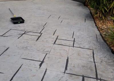 old grey concrete driveway painted black