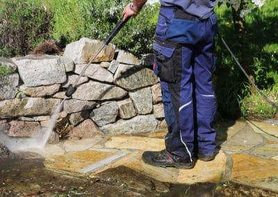 Pressure cleaning of cream sandstone tiles in garden area