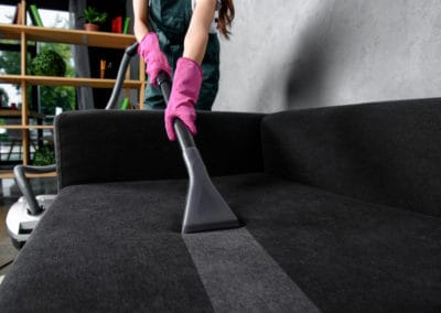 partial view of woman in rubber gloves cleaning furniture with vacuum cleaner