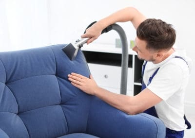 Dry cleaning worker removing dirt from armchair indoors