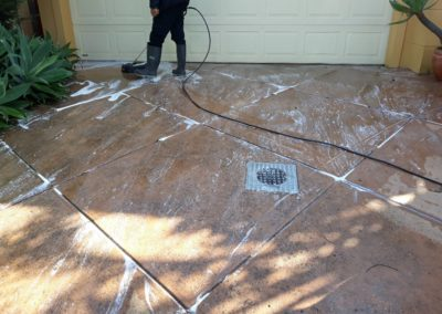 outdoor tile cleaning in progress, with white foam covering the grout